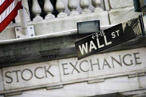 FILE - This July 16, 2013, file photo, shows a Wall Street street sign outside the New York Stock Exchange. Stock markets are mostly higher on Monday, Dec. 11, 2017, as upbeat U.S. jobs data from a week earlier and signs of progress in the Brexit talks continued to support investor sentiment. (AP Photo/Mark Lennihan, File)