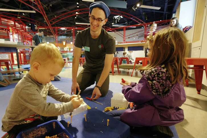 Xavian Calle (from left), 2, DoSeum maker Clint Taylor and Madeleine Lambert, 6, go to work on plastic foam at the DoSeum's Innovation Station.