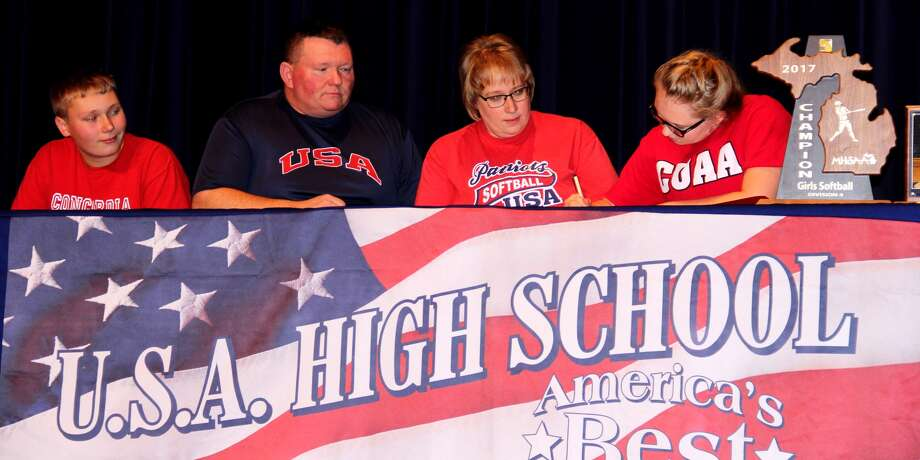 Unionville-Sebewaing Area's Hannah Volz, right, signs her letter of intent to be a student-manager for Concordia University Monday. Watching are, from left, her brother Evan, her father Warren and her mother Raylene. (Chip Burch/Huron Daily Tribune)