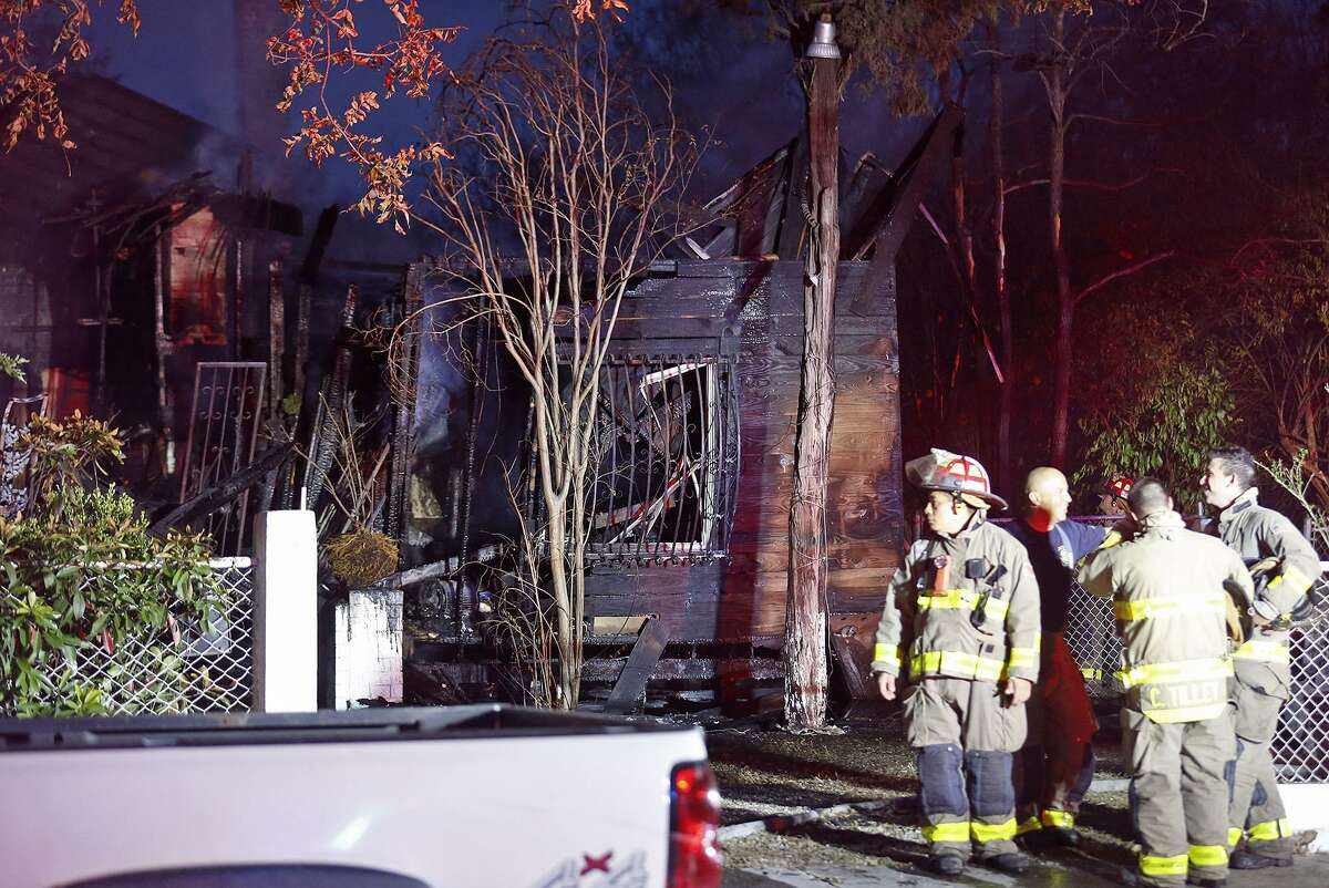 Firefighters extinguish hot spots on a home in the 2100 block of West Travis Street Monday Dec. 11, 2017.