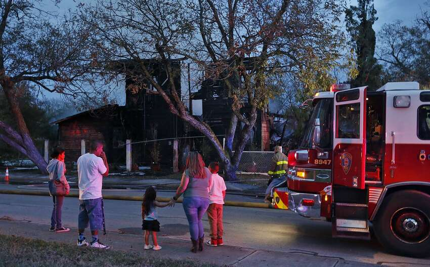 Onlookers watch firefighters extinguish hot spots on a home in the 2100 block of West Travis Street Monday Dec. 11, 2017.