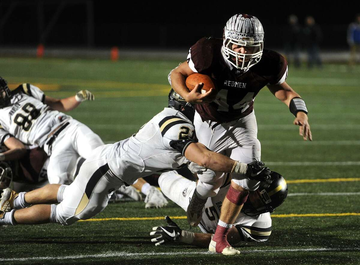 Joel Barlow defenders Alex Stillman, left, and Tyler Starrett attempt to wrap up Killingly runner Zach Caffrey in the first half of the CIAC Class M State Championship game at Veterans Stadium in New Britain, Conn. on Monday, December 11, 2017.