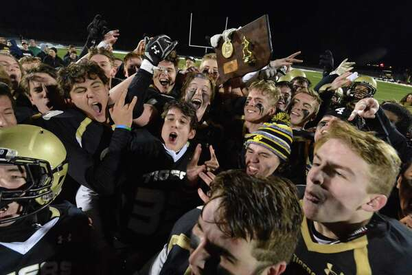 Members of the Hand football team celebrate after beating Masuk to win the Class L championship on Monday in Trumbull.