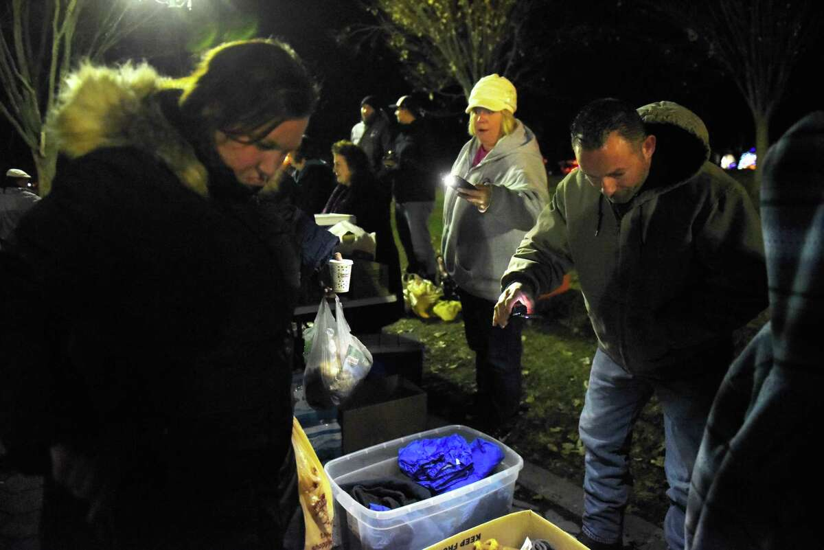 Street Soldiers shine lights on clothes for the homeless and others in need at Washington Park on Friday, Dec. 8, 2017, in Albany, N.Y. Community volunteers, who call themselves street soldiers, gather at the Washington Park memorial every Friday to distribute home-cooked food, clothes and other necessities to homeless people. (Massarah Mikati/Times Union)