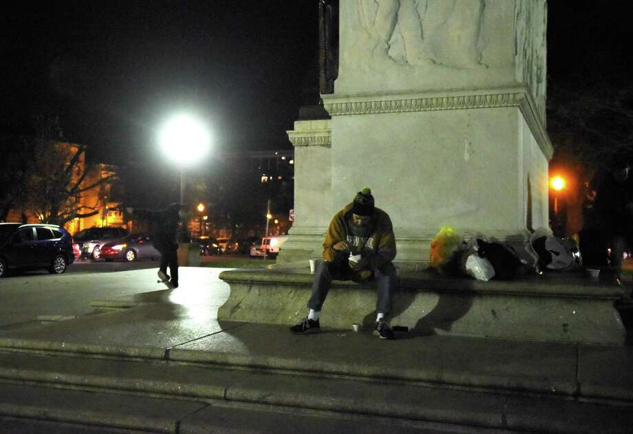A homeless man enjoys home-cooked food provided by the Street Soldiers in Washington Park at the Soldiers and Sailors? Monument on Friday, Dec. 8, 2017, in Albany, N.Y. Community volunteers, who call themselves street soldiers, gather at the Washington Park memorial every Friday to distribute home-cooked food, clothes and other necessities to homeless people. (Massarah Mikati/Times Union)