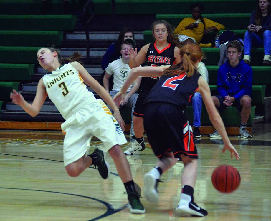 Metro-East Lutheran junior guard Sami Kasting, left, draws a charging foul in the first quarter of Monday's game against Marissa in Edwardsville.
