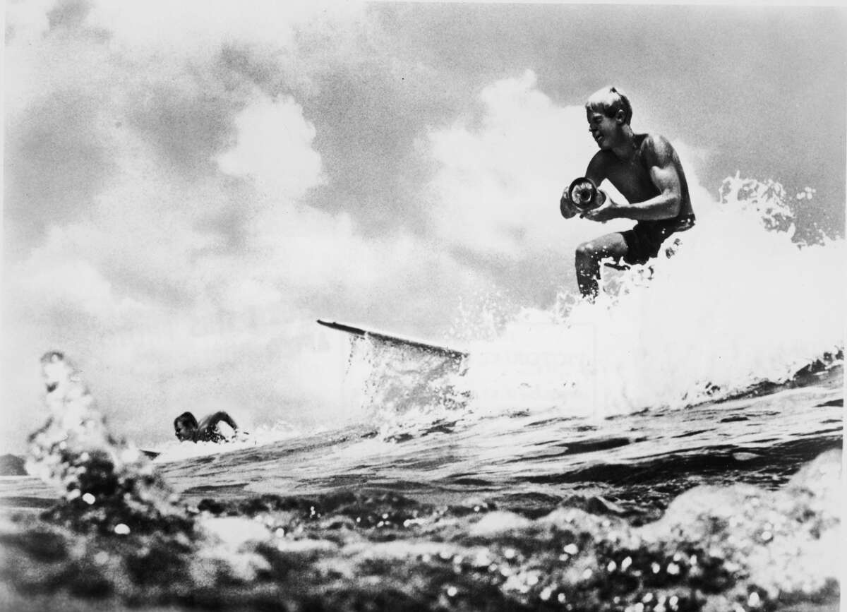 American surfer and director Bruce Brown surfs a wave and holds a camera while filming footage for his international surfing documentary, 'The Endless Summer,' circa 1966. Another surfer rides in the background. (Photo by Pictorial Parade/Getty Images)
