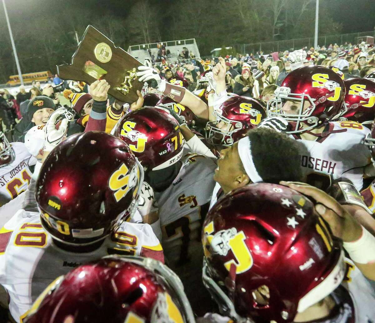 (John Vanacore/for Hearst Connecticut Media) The St Josephs Cadets celebrate their 42-36 win over Ansonia to capture the 2017 CIAC Class S football title Monday night in Cheshire