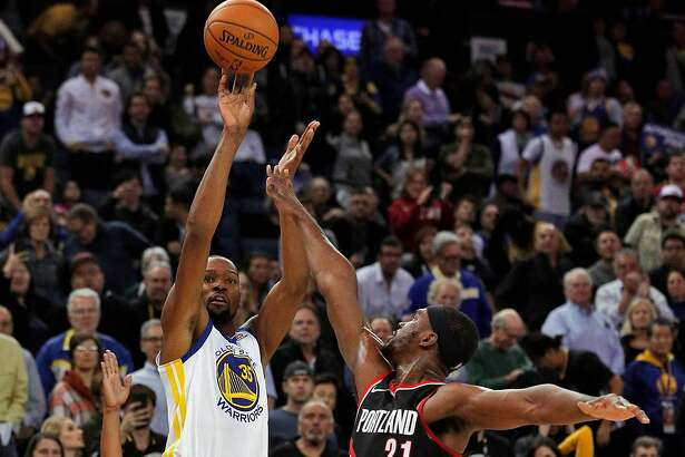 Kevin Durant (35) puts up a shot over Noah Vonleh (21) during the second half as the Golden State Warriors played the Portland Trail Blazers at Oracle Arena in Oakland, Calif., on Monday, December 11, 2017.