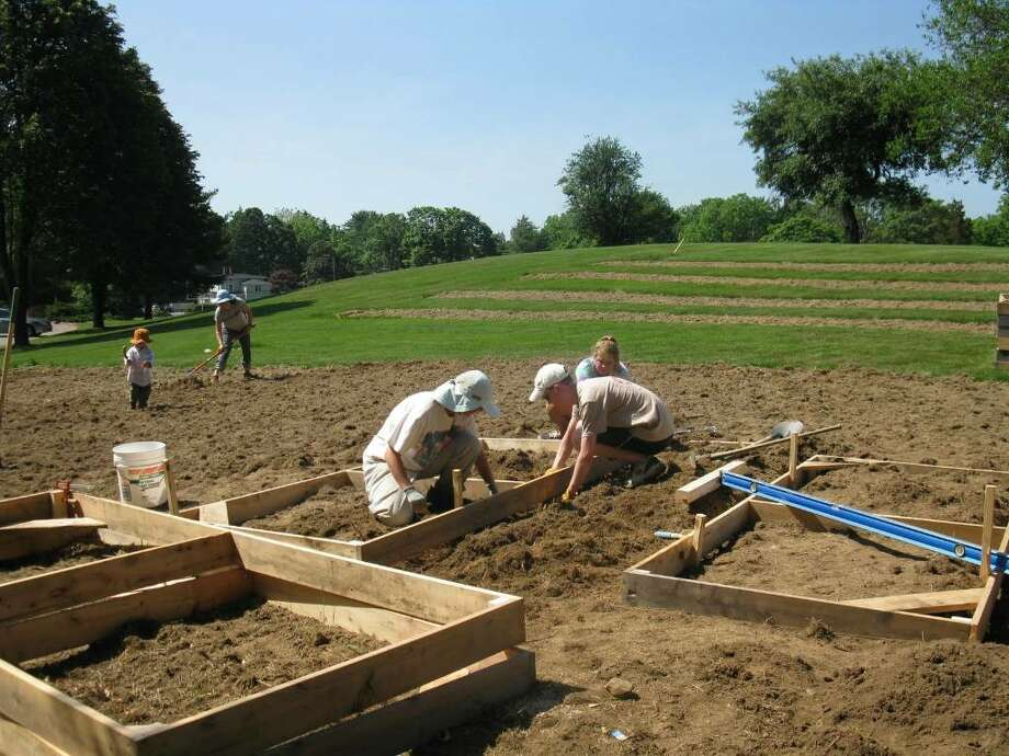 Students and faculty at Fairfield University plant the first garden on campus. Photo: Contributed Photo / Fairfield Citizen