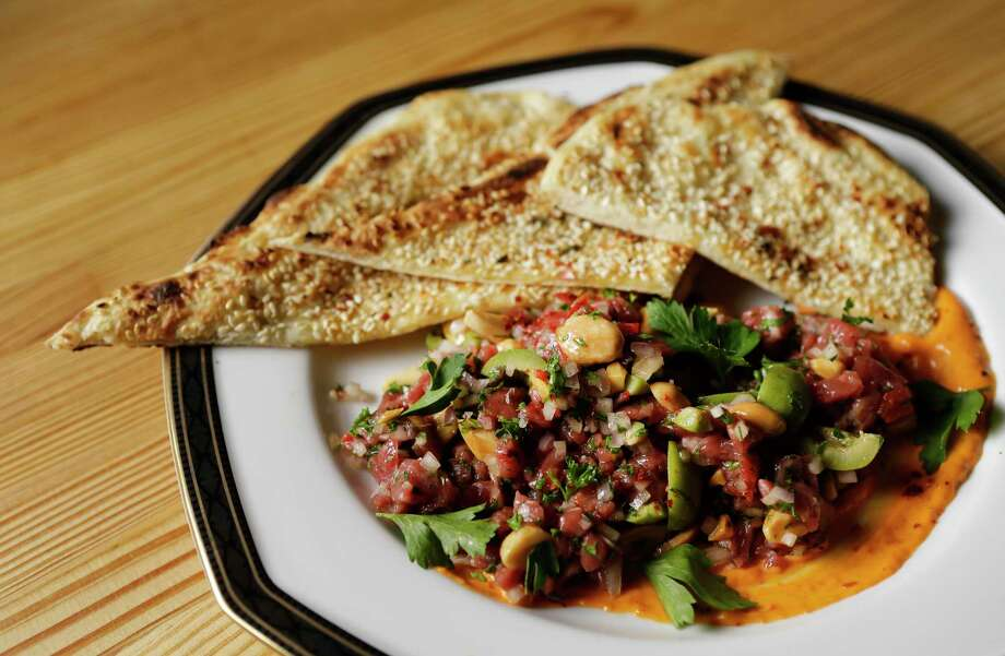Lamb tartare with green olives and almonds served with a sesame seed-crusted flat bread at Nancy's Hustle. Photo: Melissa Phillip, Houston Chronicle / © 2017 Houston Chronicle