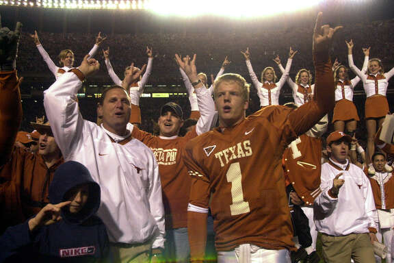 Longhorns' tight end coach Tim Brewster and Chris Simms (1) celebrate after defeating the Aggies' Friday Nov. 24, 2000 in Austin.