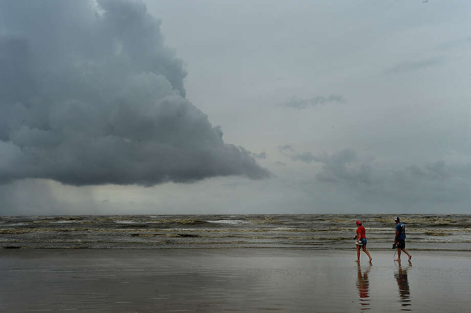 A couple strolls along the beach at McFaddin Beach as storm clouds build on the horizon the day after Hurricane Harvey made land, battering the Gulf communities surrounding Corpus Christi. Heavier rains and wind are expected to impact the Southeast Texas region within the coming days, increasing the risk for severe flooding. Photo taken Saturday, August 26, 2017 Kim Brent/The Enterprise Photo: Kim Brent / BEN