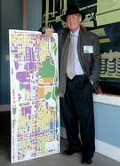 """11/20/12: Pete Brown with a map of Washington Street.  After very seriously running in 2009, architect and former city council member Peter Brown has transformed himself into Houston's leading utopian. His group, Better Houston, promotes urban planning and walkability. In on-line videos, Brown turns himself into a Stephen Colbert-like character, """"Pedestrian Pete,"""" who walks around the city with guests, chatting about the good, the bad and the ugly."""