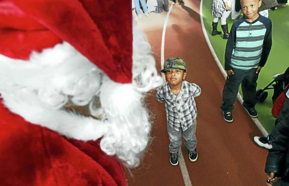 (Peter Hvizdak - New Haven Register) ¬ Todd Howell of New Haven, volunteering as Santa Claus, catches the interest of Francis Scott, 4, of New Haven, center, and other children during the City of NewHaven Winter Wonderland celebration Sunday, December 20, 2015 as the employees of the New Haven Department of Public Works coordinated toy donations in order to provide gifts for children at the theat the Floyd Little Athletic Center at Hillhouse High School. The festivities included entertainment and a dance party. ¬ Photo: Peter Hvizdak / ©2015 Peter Hvizdak / ©2015 Peter Hvizdak