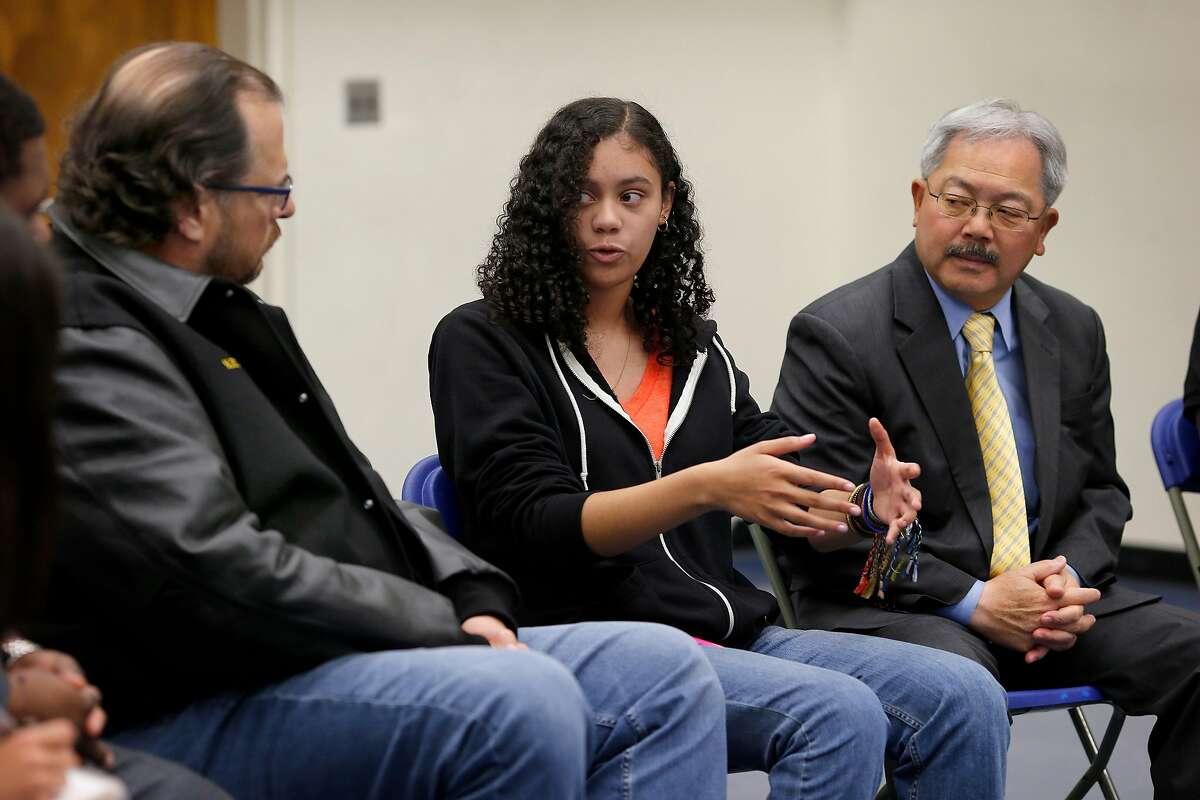 Fifteen year old Quinsi Dominguez (center) answered a question from Mark Benioff (left) as Mayor Ed Lee listened at the police academy Monday March 30, 2015. A program to expose San Francisco 18 year olds to police and fire work in the city has received new funds including a half million dollar donation from Marc Benioff of Salesforce.