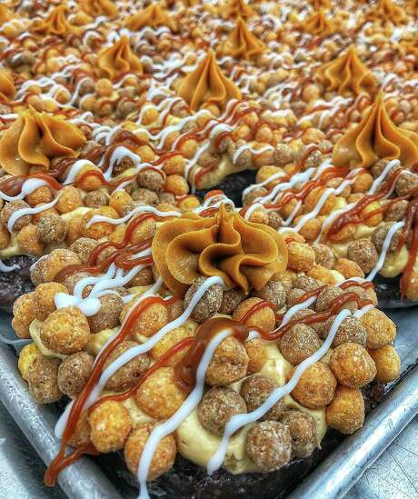 """The """"Peanut Butter Explosion"""" is a chocolate cake donut covered in peanut butter buttercream, Reese's Puffs drizzled with dulce de leche and vanilla topped with a dollop of peanut butter. Photo: Contributed/Donut Crazy"""