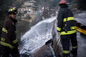 Firefighters Steve Chavez, left, and Lt. Miller mop up following a Snake Rd. fire on Tuesday, Dec. 12, 2017, in Oakland, Calif. Fueled by wind, the fire damaged multiple homes in the Oakland hills.