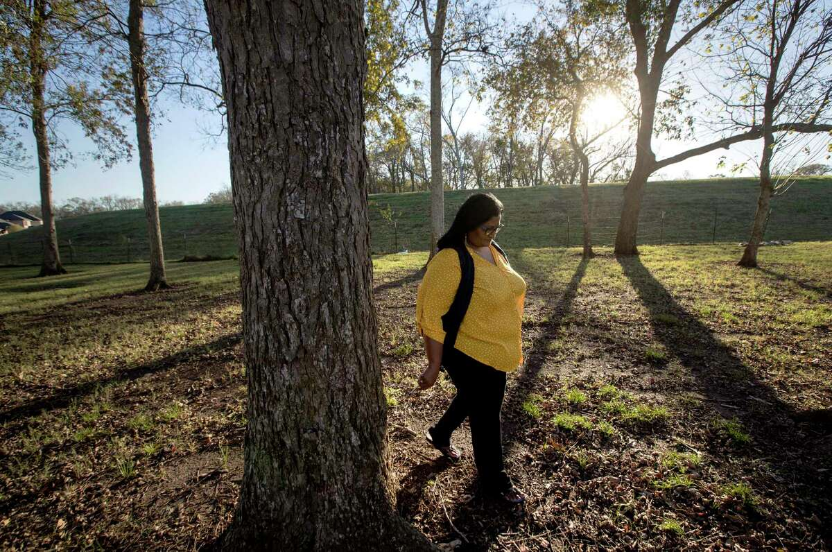 """Sailaja Koti walks near a levee that protects her house in Riverstone from the Brazos River. """"If they're not working,"""" she said, """"we are dead."""""""