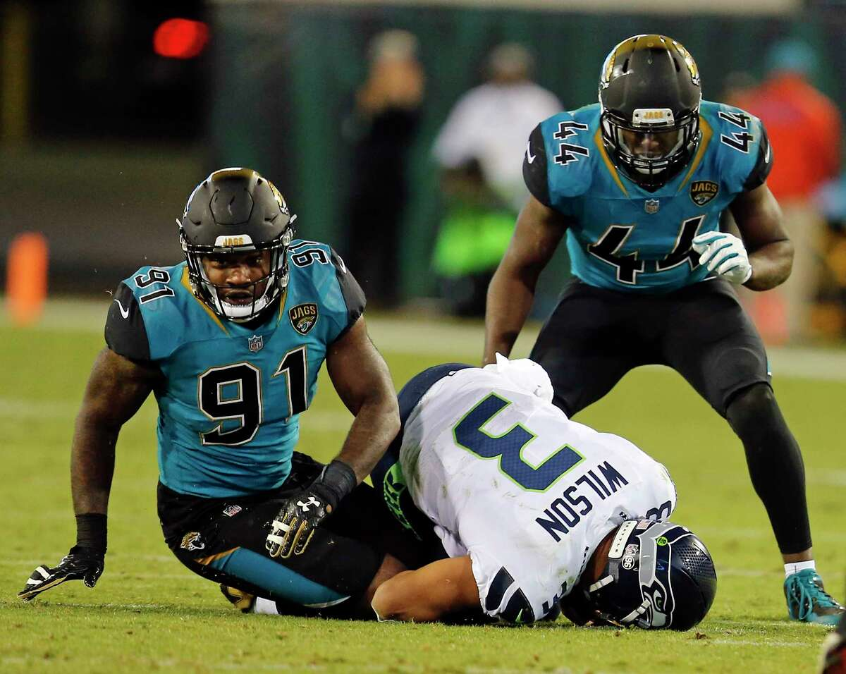 Seattle Seahawks quarterback Russell Wilson (3) is sacked by Jacksonville Jaguars defensive end Yannick Ngakoue (91) and Myles Jack (44) during the second half of an NFL football game, Sunday, Dec. 10, 2017, in Jacksonville, Fla. (AP Photo/Stephen B. Morton)