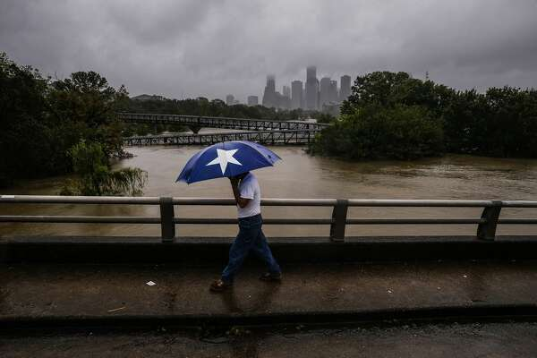 Armando Bustamante walks along Studemont Street over Buffalo Bayou as flood waters from Tropical Storm Harvey flow toward downtown Houston Tuesday, Aug. 29, 2017.