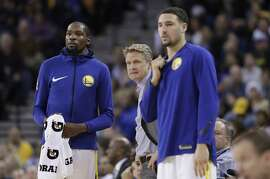 Golden State Warriors' Kevin Durant, left, head coach Steve Kerr and Klay Thompson during the second half of an NBA basketball game against the Portland Trail Blazers Monday, Dec. 11, 2017, in Oakland, Calif. (AP Photo/Marcio Jose Sanchez)