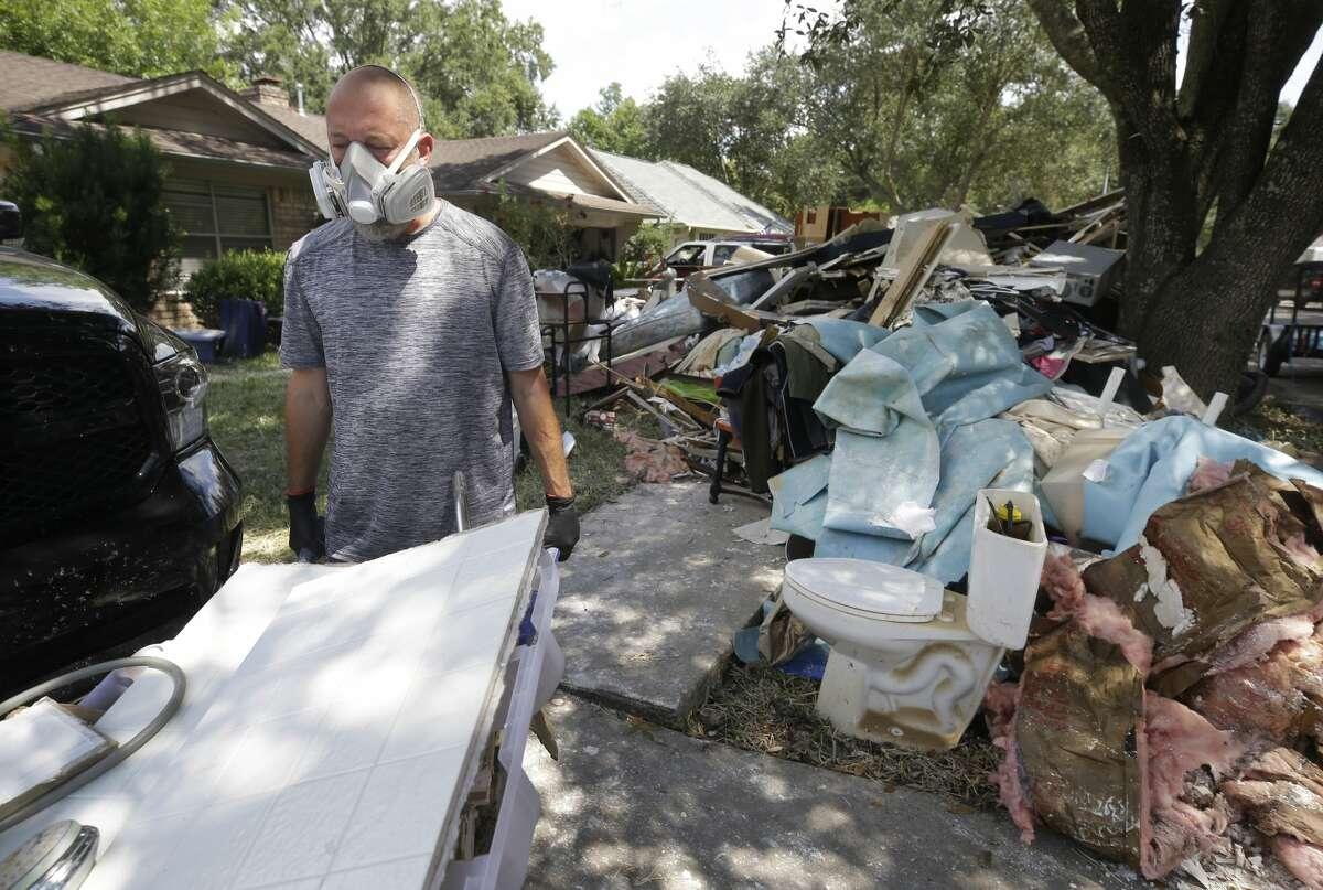 Chris Jordan helps remove debris from his next door neighbor's flooded Bear Creek Village home in the Addicks reservoir flood pool in west Houston.