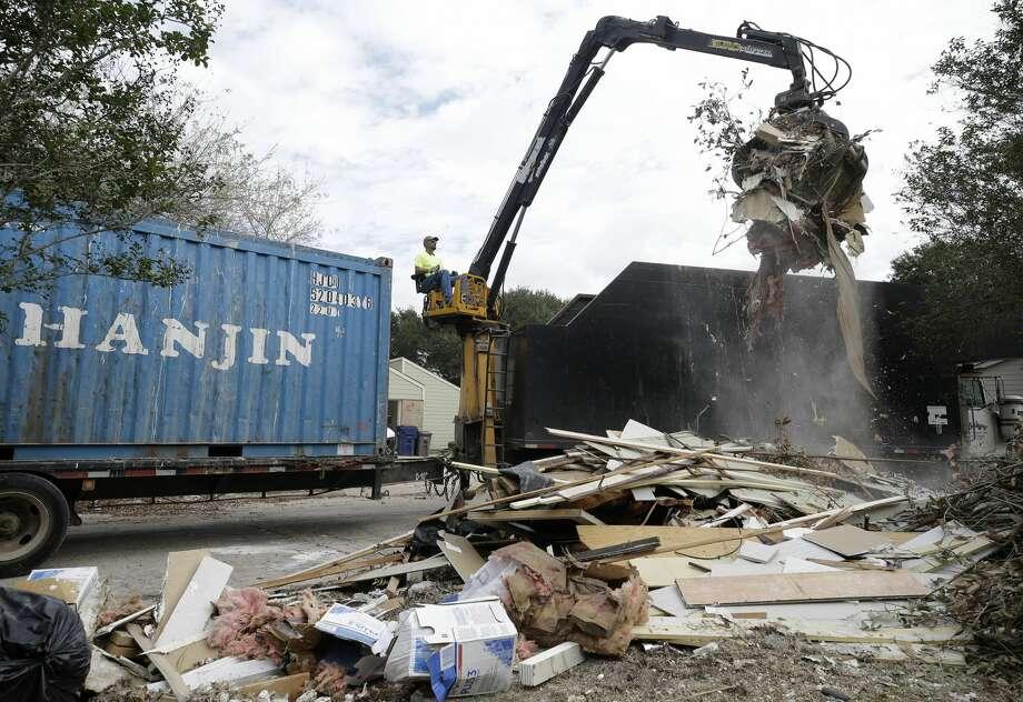 Debris are picked up in Bear Creek, a neighborhood inside the Addicks reservoir flood pool. Photo: Melissa Phillip/Houston Chronicle