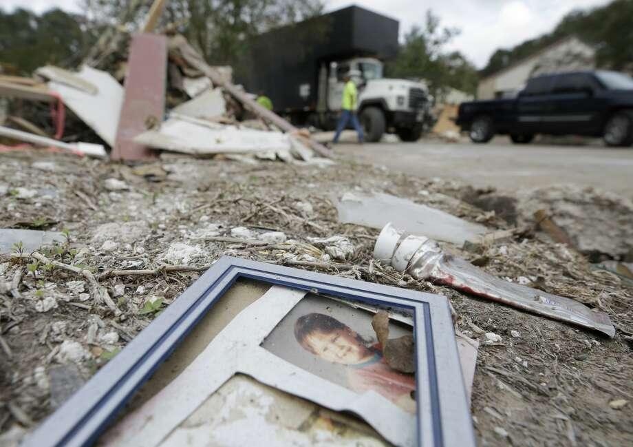 A photograph lays in the debris in Bear Creek, a neighborhood in the Addicks reservoir flood pool. Photo: Melissa Phillip/Houston Chronicle