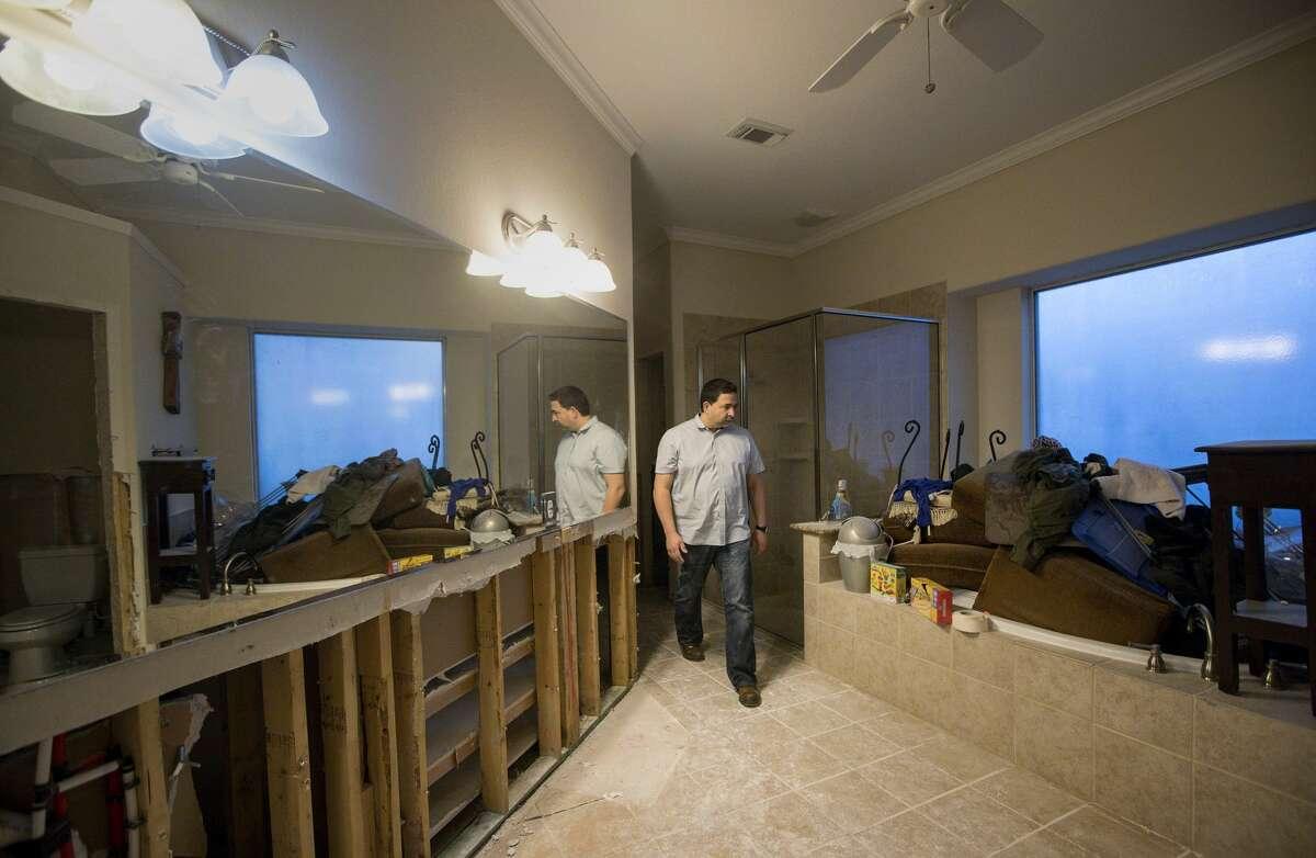 Fernando Roca prepares to leave his flood-damaged house in Katy after emptying dehumidifiers in the Kelliwood Park neighborhood near Barker reservoir.