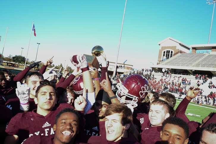 Cy Fair players hoist the trophy after defeating district rival Langham Creek 31-14 in the Class 6A Division II Region III championship game.