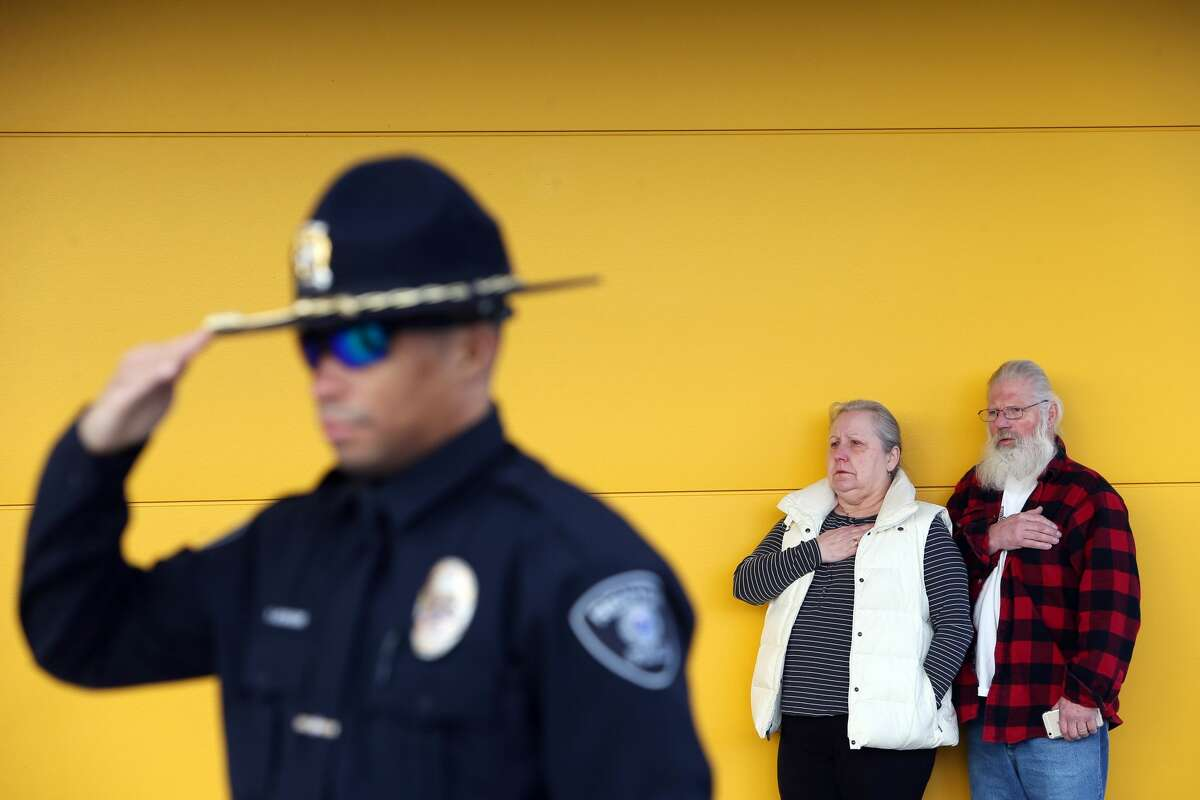 Renton police officer Robert McGruder salutes, and Sandi and Ed Johnson, of Port Angeles, hold their hands over their hearts as the national anthem is sung during an opening ceremony for for the new Ikea store in Renton on Feb. 22. The new 399,000-square-foot store replaced the old store in the same location and includes a children's play area, a 600-seat restaurant that offers a full Swedish breakfast and, at 244,000 square feet, the state's largest rooftop solar panel array.