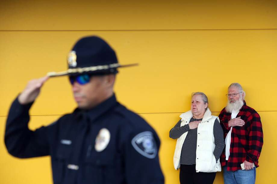 Renton police officer Robert McGruder salutes, and Sandi and Ed Johnson, of Port Angeles, hold their hands over their hearts as the national anthem is sung during an opening ceremony for  for the new Ikea store in Renton on Feb. 22. The new 399,000-square-foot store replaced the old store in the same location and includes a children's play area, a 600-seat restaurant that offers a full Swedish breakfast and, at 244,000 square feet, the state's largest rooftop solar panel array. Photo: GENNA MARTIN/SEATTLEPI