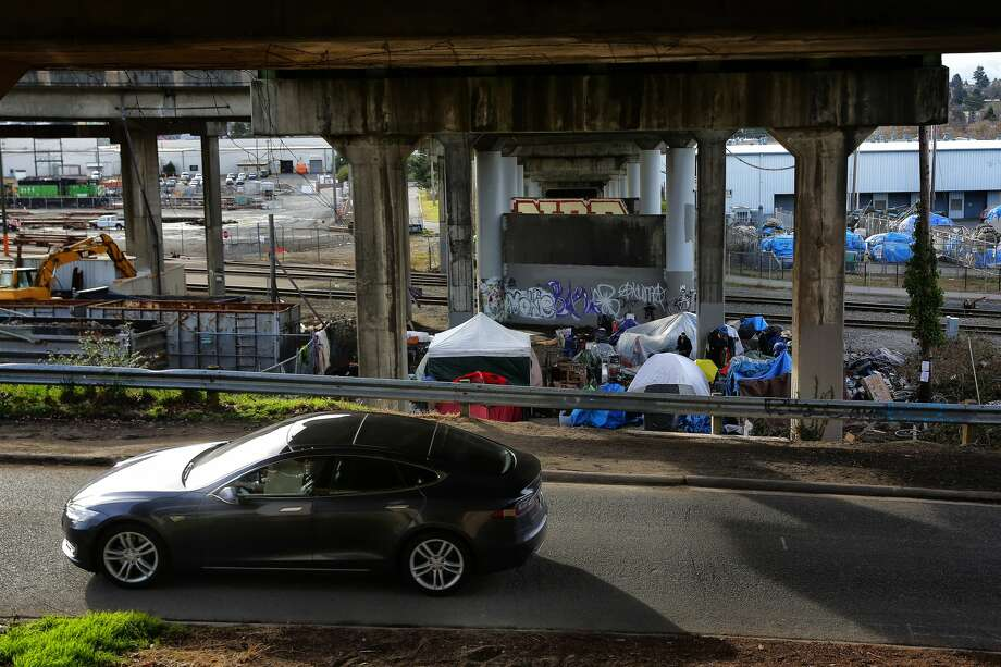A Tesla drives past a homeless encampment under the south end of the Ballard Bridge, March 1, 2017. The city announced plans this week to clear the camp away. About six people are still living at the camp. (Genna Martin, seattlepi.com) Photo: GENNA MARTIN/SEATTLEPI