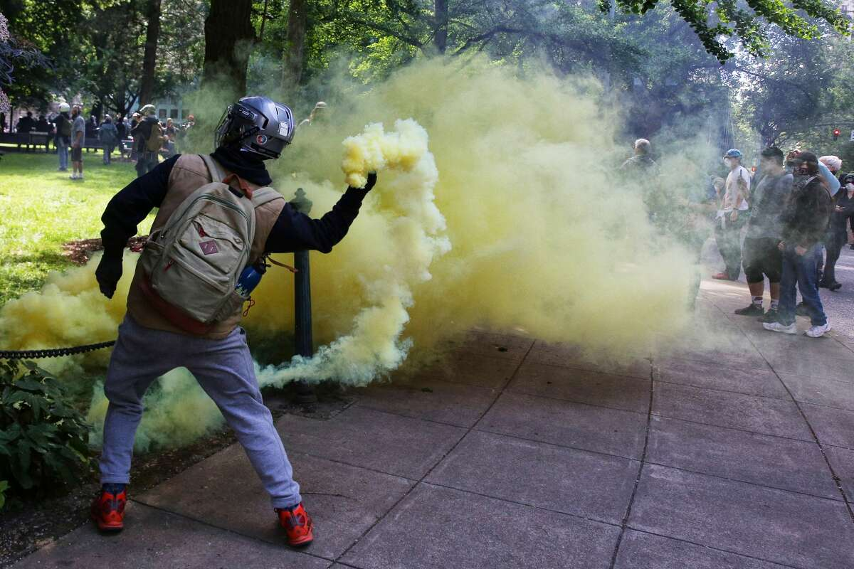 A counter-protester throws a smoke bomb back towards police as law enforcement clears Chapman Park across the street from a