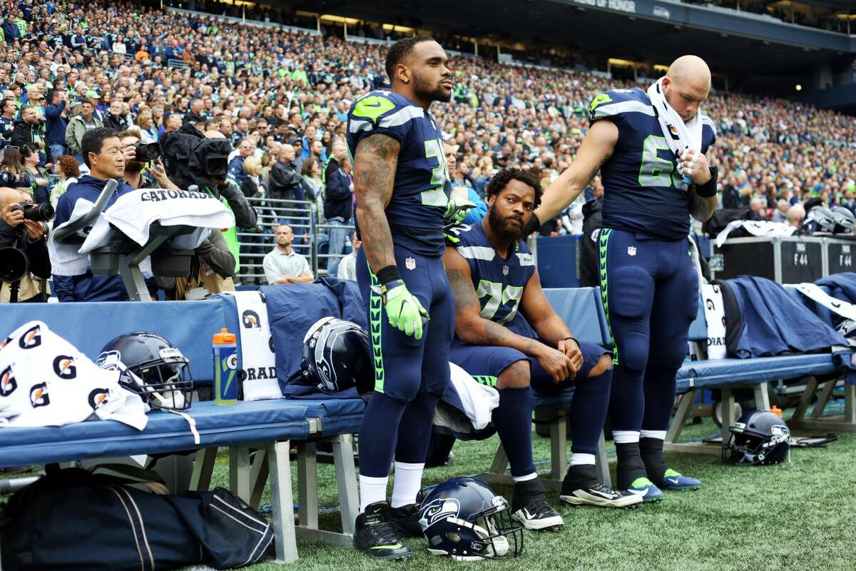 Thomas Rawls, left, and Justin Britt, right, stand on either side of Seahawks defensive lineman Michael Bennett as he sits for the National Anthem as a continued protest against police brutality, before Seattle's game against San Francisco, Sunday, Sept. 17, 2017. (Genna Martin, seattlepi.com)