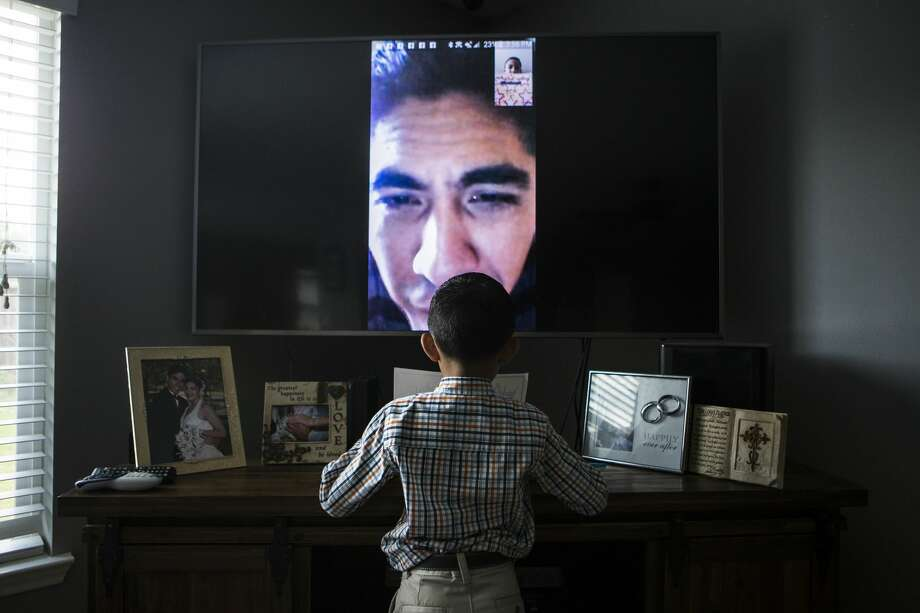 Jose Escobar, who lived in the U.S. for almost two decades, watches from El Salvador as his 7-year-old son opens kindergarten graduation gifts. The father of two and husband of an American citizen came to Houston with his mother as a teen but lost his legal status through a clerical error. He was deported under new federal guidelines. Photo: Marie D. De Jesús