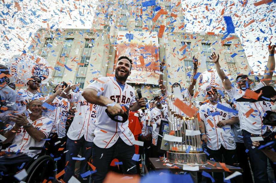 Star second baseman Jose Altuve joyfully tosses a World Series cap into the crowd in front of City Hall during the celebration honoring the Astros and their world championship. Confetti rained over the team – and Gov. Greg Abbott, appropriately attired in an Astros jersey – and for a moment obscured the trophy that eluded the organization since becoming a major league team in 1962. Photo: Brett Coomer