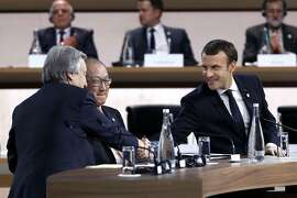 """French President Emmanuel Macron (R) shakes hands with United Nations (UN) Secretary General Antonio Guterres during the One Planet Summit on December 12, 2017, at La Seine Musicale venue on the ile Seguin in Boulogne-Billancourt, southwest of Paris. ?The French President hosts 50 world leaders for the """"One Planet Summit"""", hoping to jump-start the transition to a greener economy two years after the historic Paris agreement to limit climate change. / AFP PHOTO / POOL / Etienne LAURENTETIENNE LAURENT/AFP/Getty Images"""
