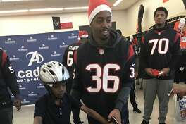 Houston Texans rookie cornerback Josh Thornton helps a child try out a bike while offensive lineman Julien Davenport watches during a shopping spree at Academy Sports + Outdoors gave 14 children from the Houston YMCA and the Boys & Girls Club of Greater Houston a shopping spree at Academy Sports + Outdoors on Tuesday morning.