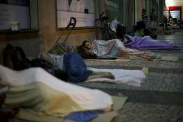 In this Dec. 6, 2017 photo, homeless people sleep outside the public defenders office in Rio de Janeiro, Brazil. Warm temperatures and miles of beaches have long made Brazil�s most famous city a place with a large street population, but city officials say it�s more than tripled in the last few years. (AP Photo/Silvia Izquierdo)