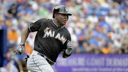 Miami Marlins' Marcell Ozuna heads to first with a single during the first inning of an exhibition spring training baseball game against the New York Mets Friday, March 4, 2016, in Port St. Lucie, Fla. (AP Photo/Jeff Roberson)