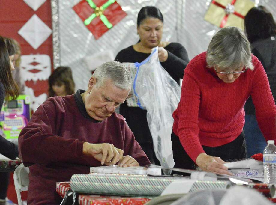 Ron Domonkos of Stamford and his wife Carmen, a member of Inspirica's Board of Directors, join a brigade of volunteers as they wrap some 6,000 personalized holiday gifts for 3,000 children in Fairfield County at Inspirica in Stamford, Conn. on Dec. 9, 2017. The recipients of the gifts are kids impacted by poverty, AIDS and homelessness. Photo: Matthew Brown / Hearst Connecticut Media / Stamford Advocate