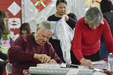 Ron Domonkos of Stamford and his wife Carmen, a member of Inspirica's Board of Directors, join a brigade of volunteers as they wrap some 6,000 personalized holiday gifts for 3,000 children in Fairfield County at Inspirica in Stamford, Conn. on Dec. 9, 2017. The recipients of the gifts are kids impacted by poverty, AIDS and homelessness.