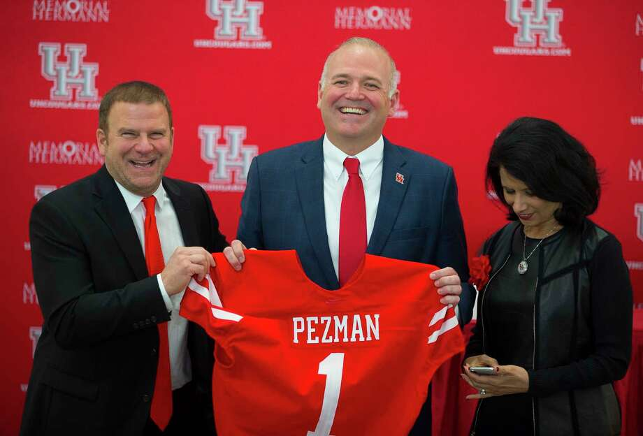 PHOTOS: A look at Chris Pezman's introductory press conferenceUniversity of Houston board chairman Tilman Fertitta (left) and university chancellor Renu Khator (right) pose for photos with new athletic director Chris Pezman following an introductory press conference at TDECU Stadium, Tuesday, Dec. 12, 2017, in Houston. Photo: Mark Mulligan, Houston Chronicle / © 2017 Houston Chronicle