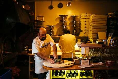 Erasto Franco cuts a pizza into slices at Tommaso's in North Beach. Photo: Mason Trinca / Special To The Chronicle 2017