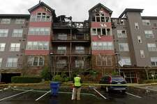 Residents of Stonewood Condominiums at 100 Richards Ave. evacuate with their pets Tuesday, December 12, 2017, following a fire there Monday night in Norwalk, Conn.