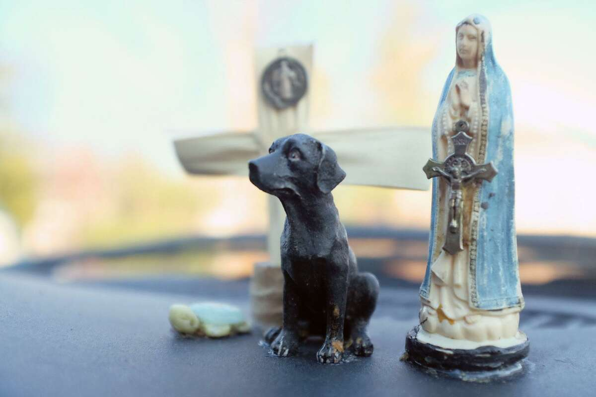 """A cross and figurines of Saint Mary, a turtle and a black lab grace the dashboard of the van where Joe had been living with his dog, Bronson. """"To ward off bad spirits,""""Joe said on Dec. 4, 2017. Having a pet can make finding a shelter more difficult,since many shelters do not accept pets for safety and allergy reasons. Bronson recently passed away, shortly before Joe found permanent supportive housing."""