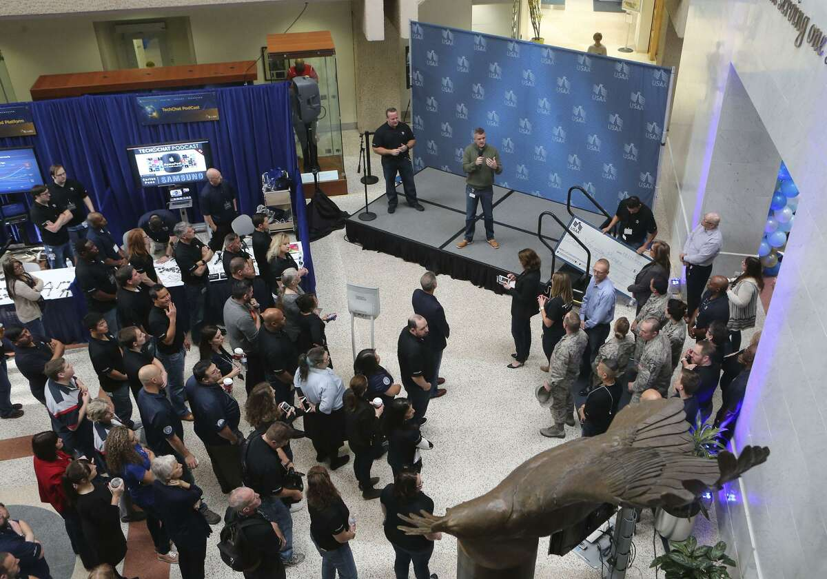 Sean Burgess (holding microphone) and Zack Gipson (left), USAA's chief innovation officer, take the stage Tuesday as products and works in progress are displayed. Gipson says 92 percent of the company's employees participate in some way in the innovation activities. Employees have submitted 8,896 ideas so far.