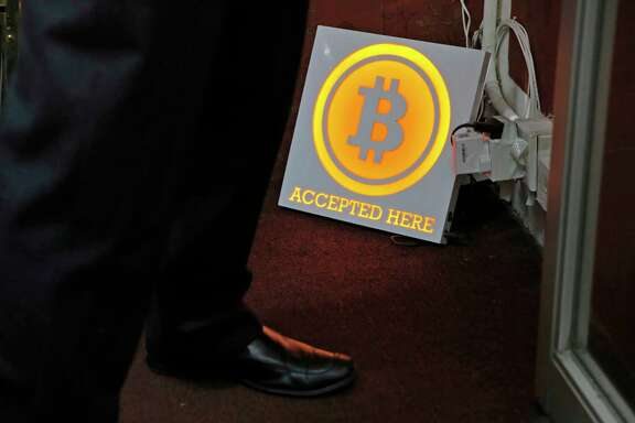 In this Friday, Dec. 8, 2017, photo, a man stands besides a Bitcoin sign near a Bitcoin ATM in Hong Kong. The launch of a U.S. futures contract for bitcoin on Sunday, Dec. 10, 2017, underscores the virtual currency's increasing mainstream acceptance, including in many parts of Asia, where it already has a wide following among speculators and investors. (AP Photo/Kin Cheung)